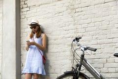 Concepto de la vida de ciudad Mujer joven que se coloca al lado de la pared de ladrillo blanca que escucha la música en auricular fotografía de archivo libre de regalías