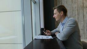 Concepto de la vida del estudiante Un estudiante masculino se sienta en el wimdow panaramic con un teléfono a disposición brainst metrajes