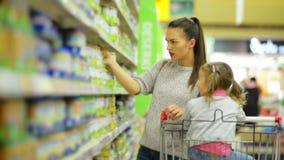 Concepto de las compras de la familia Retrato de la mujer y de la muchacha sonrientes que eligen productos en tienda de alimentos almacen de video