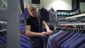 Concepto de las compras y de la moda - chaqueta que elige y que intenta del hombre joven encendido en tienda de la alameda o de r almacen de video