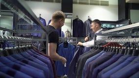 Concepto de las compras y de la moda - chaqueta que elige y que intenta del hombre joven encendido en tienda de la alameda o de r metrajes