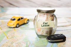 Concepto de las finanzas del coche - vidrio del dinero con el arriendo del coche de la palabra, llave del coche foto de archivo