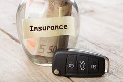 Concepto de las finanzas del coche - vidrio del dinero con el seguro de la palabra, llave del coche foto de archivo libre de regalías