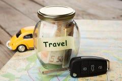 Concepto de las finanzas del coche - vidrio del dinero con el viaje de la palabra, llave del coche y imágenes de archivo libres de regalías