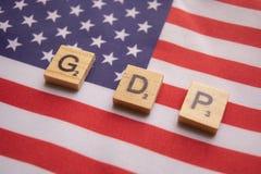 Concepto de las finanzas, GDP o letras de molde de madera del producto interno bruto en bandera del dólar americano foto de archivo