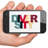 Concepto de las finanzas: Mano que sostiene Smartphone con diversidad en la exhibición imagen de archivo
