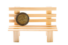Concepto de las finanzas Moneda del euro dos en el banco de madera decorativo aislado en blanco fotos de archivo