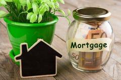 Concepto de las finanzas de las propiedades inmobiliarias - vidrio del dinero con palabra de la hipoteca imágenes de archivo libres de regalías