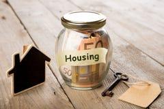 Concepto de las finanzas de las propiedades inmobiliarias - vidrio del dinero con palabra de la vivienda fotografía de archivo