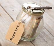 Concepto de las finanzas de las propiedades inmobiliarias - vidrio del dinero con palabra del pago foto de archivo