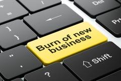 Concepto de las finanzas: Quemadura del nuevo negocio en fondo del teclado de ordenador fotos de archivo libres de regalías