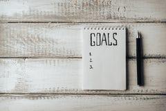 Concepto de las metas El cuaderno con metas enumera té en la tabla de madera Motivación Imagen de archivo libre de regalías