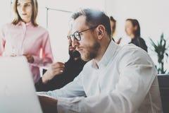 Concepto de las personas del asunto Los profesionales jovenes que discuten nuevo negocio proyectan en oficina moderna El grupo de imagen de archivo