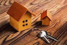 Concepto de las propiedades inmobiliarias con la casa y llave en fondo de madera Concepto del estado de la idea de verdad, propie imagenes de archivo