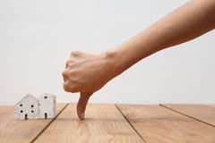 Concepto de las propiedades inmobiliarias una mano que muestra el pulgar abajo en la casa miniatura Foto de archivo