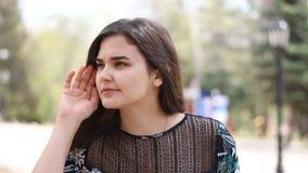 Concepto de las rumores, del chisme y de los gestos Mujer morena que escucha cuidadosamente con la mano cerca del oído almacen de video