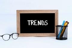 Concepto de las tendencias escrito en la pizarra para el negocio con la caja de los vidrios, del marcador y de la pluma foto de archivo