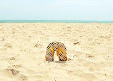 Concepto de las vacaciones de verano Flip-flop en una playa arenosa del océano Foto de archivo libre de regalías