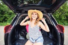 Concepto de las vacaciones, del viaje - mujer joven lista para el viaje el vacaciones de verano con las maletas y coche Imágenes de archivo libres de regalías