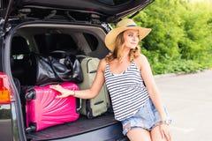 Concepto de las vacaciones, del viaje - mujer joven lista para el viaje el vacaciones de verano con las maletas y coche Foto de archivo libre de regalías