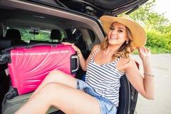 Concepto de las vacaciones, del viaje - mujer joven lista para el viaje el vacaciones de verano con las maletas y coche Fotografía de archivo libre de regalías