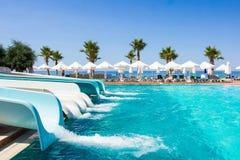 Concepto de las vacaciones - diapositivas y piscina en aquapark Imagen de archivo libre de regalías