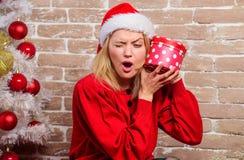Concepto de las vacaciones de invierno Excitado sobre presente Vestido de la muchacha cerca del árbol de navidad Desempaque del r fotos de archivo libres de regalías