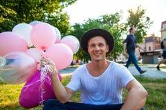 Concepto de las vacaciones de verano, de la celebración y de la forma de vida - hombre con los globos coloridos en la ciudad fotos de archivo