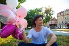Concepto de las vacaciones de verano, de la celebración y de la forma de vida - hombre con los globos coloridos en la ciudad fotografía de archivo
