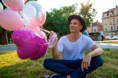 Concepto de las vacaciones de verano, de la celebración y de la forma de vida - hombre con los globos coloridos en la ciudad imagen de archivo