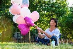 Concepto de las vacaciones de verano, de la celebración y de la forma de vida - hombre con los globos coloridos en la ciudad fotografía de archivo libre de regalías