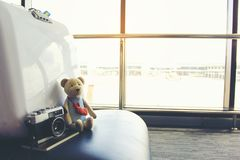 Concepto de las vacaciones de verano, oso de peluche con el pasaporte y las sillas vacías y pasajero en el terminal de aeropuerto imagenes de archivo