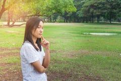 Concepto de las vacaciones y del día de fiesta: Camiseta blanca que lleva de la mujer Ella que se coloca en hierba verde en el pa fotos de archivo