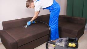 Concepto de limpieza en el apartamento y la oficina Trabajador de la limpieza en seco que quita la suciedad del sofá dentro almacen de metraje de vídeo