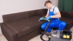 Concepto de limpieza en el apartamento y la oficina Trabajador de la limpieza en seco que quita la suciedad del sofá dentro metrajes