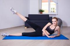 Concepto de los aeróbicos - adelgace a la mujer flexible que hace estirando ejercicio Imágenes de archivo libres de regalías