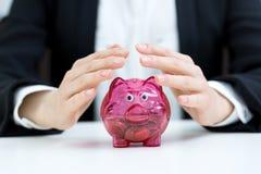 Concepto de los ahorros del negocio - ingenio de la hucha de la cubierta de la empresaria Imágenes de archivo libres de regalías