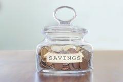 Concepto de los ahorros Tarro de cristal por completo de monedas Imagenes de archivo