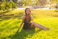Concepto de los auriculares La muchacha hermosa que se relaja y escucha música en los auriculares en el parque de la ciudad en fo Foto de archivo