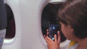 Concepto de los aviones de la aviaci?n la chica joven está volando en un avión dentro de toma imágenes en la ciudad de la noche d almacen de metraje de vídeo