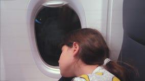 Concepto de los aviones de la aviaci?n niña joven que duerme en el aeroplano que se sienta por la ventana vuelo en la noche cerca almacen de video