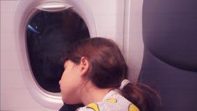 Concepto de los aviones de la aviaci?n ni?a joven que duerme en el aeroplano que se sienta por la ventana vuelo en la noche en av metrajes