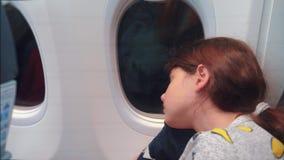 Concepto de los aviones de la aviaci?n ni?a joven que duerme en el aeroplano que se sienta por la ventana vuelo en la noche cerca almacen de video