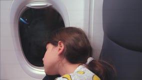 Concepto de los aviones de la aviaci?n ni?a joven que duerme en el aeroplano que se sienta por la ventana vuelo en la noche de la almacen de metraje de vídeo