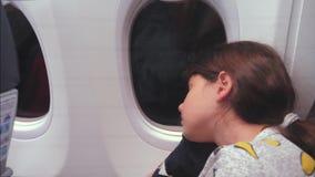 Concepto de los aviones de la aviaci?n ni?a joven que duerme en el aeroplano que se sienta por la ventana vuelo en la noche en ae almacen de video