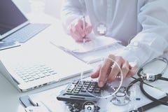 Concepto de los costes y de las tarifas de la atención sanitaria La mano del doctor elegante utilizó un Ca fotos de archivo