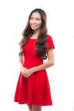 Concepto de los días de fiesta, de la celebración y de la gente - mujer sonriente en vestido rojo en el fondo blanco Imagenes de archivo