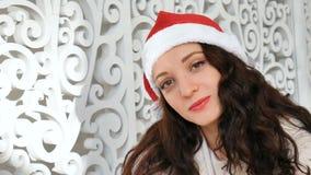 Concepto de los días de fiesta y de la gente - mujer hermosa en el sombrero de santa y y el pelo rizado que sonríe contra el cont metrajes