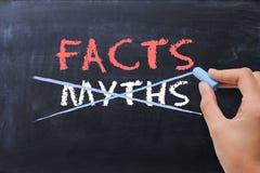 Concepto de los mitos o de los hechos con el dibujo de la mano de la mujer de negocios en la pizarra imagen de archivo