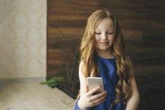 Concepto de los niños, de la tecnología y de la comunicación - muchacha sonriente que manda un SMS en smartphone en casa Foto de archivo